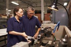 Ingeniero Training Female Apprentice en la fresadora imágenes de archivo libres de regalías