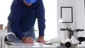 Ingeniero Working en el drenaje de la oficina y modificar planes y proyectos metrajes