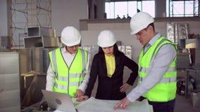 Ingeniero y cliente que miran en proyecto sobre el emplazamiento de la obra 4 K metrajes