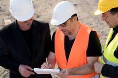 Ingenieros civiles que escriben en un cuaderno fotos de archivo libres de regalías