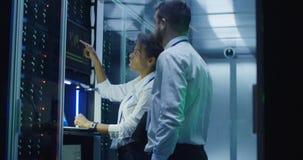 Ingenieros de las TIC con los dispositivos coworking en centro de datos fotos de archivo libres de regalías