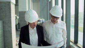 Ingenieros ejecutivos de sexo masculino y de sexo femenino en cascos que caminan alrededor de taller de la fábrica y que lo discu almacen de video
