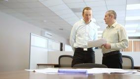 Ingenieros en la oficina para discutir los documentos en el fondo de la tabla con los documentos almacen de metraje de vídeo