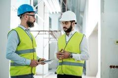 Ingenieros en los cascos de protección que tienen conversación foto de archivo