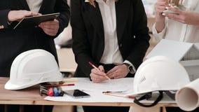 Ingenieros en los trajes de negocios, colocándose cerca de una tabla de trabajo en que ponga los modelos, casco, lápices, marcado almacen de metraje de vídeo