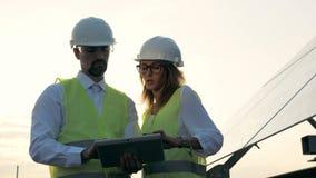 Ingenieros en tipo uniforme en una tableta junto, colocándose cerca de los paneles solares Alternativa, concepto verde de la ener metrajes