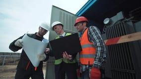 Ingenieros en un uniforme cerca del transformador de corriente foto de archivo