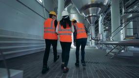 Ingenieros en uniforme que caminan en una cervecería, visión trasera almacen de metraje de vídeo
