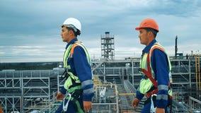 Ingenieros industriales que caminan a través del borde superior de un tejado metrajes