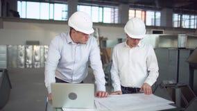 Ingenieros o arquitectos que tienen una discusión en el emplazamiento de la obra aeroducto de un sistema de la HVAC metrajes