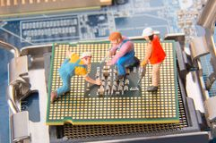 Ingenieros o trabajadores miniatura del técnico que reparan la CPU en la placa madre Servicio informático y concepto de la tecnol fotos de archivo libres de regalías