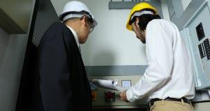 Ingenieros que comprueban el gabinete de control eléctrico