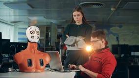 Ingenieros que controlan un droid, usando un ordenador portátil, cierre para arriba metrajes