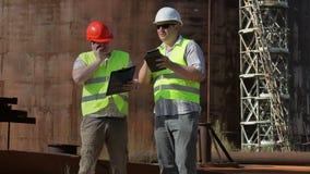 Ingenieros que hablan en el tanque cercano al aire libre