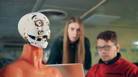 Ingenieros que miran un droid el levantarse de la cara, cierre almacen de metraje de vídeo