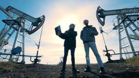 Ingenieros que se colocan en un campo petrolífero en un fondo del sol, visión inferior almacen de metraje de vídeo