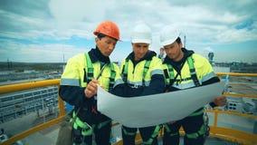 Ingenieros y trabajadores que planean el trabajo en planta industrial metrajes