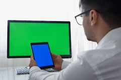 Ingenieur, Aannemer, Ontwerper in Glazen die aan een Personal computer met het Groen Scherm op Monitor werken dat heeft stock foto