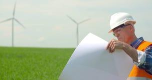 Ingenieur Analyzing Plan While die Windmolenlandbouwbedrijf bekijken De energieconcept van Eco stock videobeelden