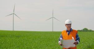 Ingenieur Analyzing Plan While die Windmolenlandbouwbedrijf bekijken De energieconcept van Eco stock video