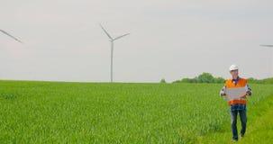 Ingenieur Analyzing Plan While die Windmolenlandbouwbedrijf bekijken De energieconcept van Eco stock footage
