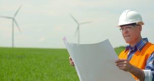 Ingenieur Analyzing Plan While die Windmolens in Landbouwbedrijf bekijken stock video