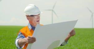 Ingenieur Analyzing Plan While die Windmolens in Landbouwbedrijf bekijken stock footage