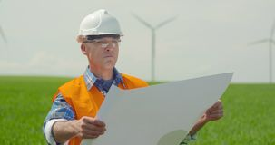 Ingenieur Analyzing Plan While die Windmolens in Landbouwbedrijf bekijken stock videobeelden