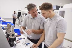 Ingenieur And Apprentice Discussing Job Sheet In Factory royalty-vrije stock foto's