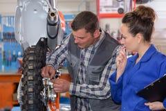 Ingenieur And Apprentice Working op Machine in Fabriek stock foto's