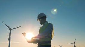 Ingenieur arbeitet an einem Sonnenunterganghintergrund Windmühlen, grünes Energiekonzept stock video