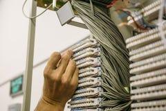 Ingenieur arbeitet im Rechenzentrum mit Kabeln und Schaltern stockbilder
