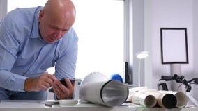 Ingenieur in Architektur-Büro-Lächeln-lesenden guten Nachrichten auf Smartphone stock video
