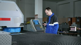 Ingenieur bij de fabriek met een telefoon in zijn hand over ponsen van de machine CNC Het detail beweegt zich in verschillend stock videobeelden