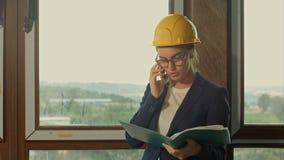 Ingenieur bij een bouwwerf die zaken maken roepen stock footage