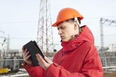 Ingenieur bij elektrohulpkantoor die een tabletcomputer met behulp van Royalty-vrije Stock Afbeelding