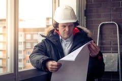 Ingenieur-bouwer die met documenten aan de bouwwerf werken De arbeider inspecteert tekeningen op de bouwwerf stock fotografie
