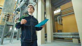 Ingenieur in bouwvakker die in fabriek lopen en op klembord neerschrijven stock video