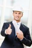 Ingenieur in de blauwdruk en de duimen van bouwvakkerhanden omhoog Stock Foto's