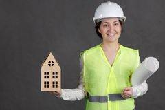 Ingenieur der jungen Frau im Schutzhelm und Weste mit Dokumenten und Modell in den Händen lizenzfreie stockfotografie