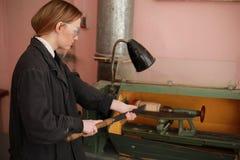 Ingenieur der jungen Frau, der an der Werkzeugmaschine arbeitet stockfotos
