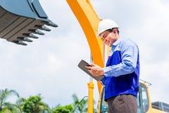 Ingenieur, der Pläne auf Baustelle überprüft Lizenzfreies Stockbild