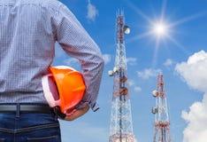 Ingenieur, der Schutzhelm mit Telekommunikationsturmsäulen hält Lizenzfreies Stockfoto