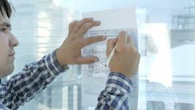 Ingenieur die aan blauwdruk in een modern bureau werken stock footage