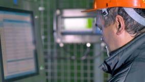 Ingenieur die binnen aan het computerscherm industriële fabriek bekijken 4K stock video