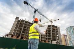 Ingenieur die in bouwvakker in aanbouw de bouw bekijken Royalty-vrije Stock Afbeelding