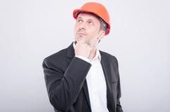 Ingenieur die bouwvakker dragen die het denken gebaar maken Stock Foto
