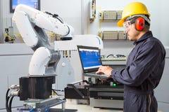 Ingenieur die computer voor de onderhouds automatische robotachtige industrie met behulp van stock foto