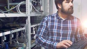 IT ingenieur die in de fabriek van de cryptocurrencymijnbouw werken Industrieel mijnbouwlandbouwbedrijf voor bitcoin en cryptocur stock footage