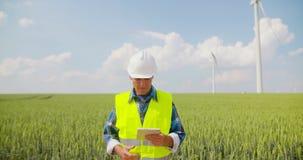 Ingenieur die digitale tablet op het landbouwbedrijf van de windturbine gebruiken stock videobeelden